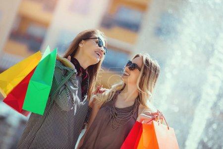 Photo pour Des amis heureux faisant du shopping. Jeunes amis qui aiment faire du shopping en ville, tenir des sacs à provisions . - image libre de droit