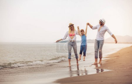 happy young family have fun on beach, run and jump
