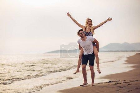 Photo pour Joyeuse jeune femme ferroutage sur jeune copain et s'amuser. - image libre de droit