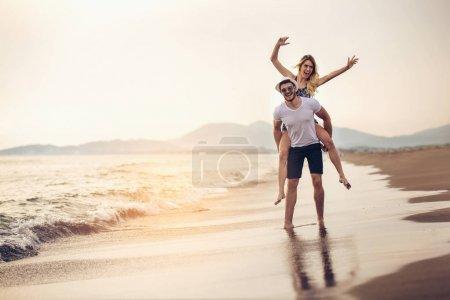 Photo pour Joyeuse jeune femme piggyback sur jeune copain et avoir du plaisir . - image libre de droit