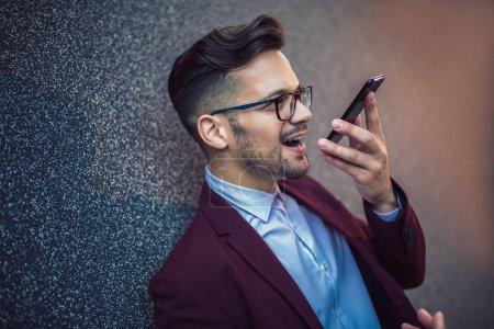 Photo pour Jeune homme d'affaires utilisant l'enregistreur de commande vocale sur le smartphone. - image libre de droit