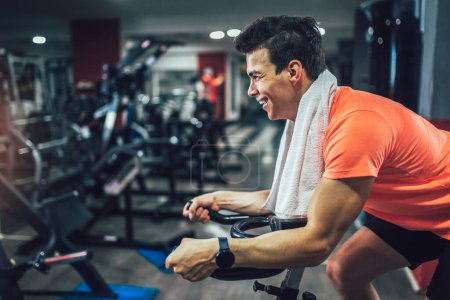 Photo for Man biking in the gym, exercising legs doing cardio workout cycling bikes. - Royalty Free Image