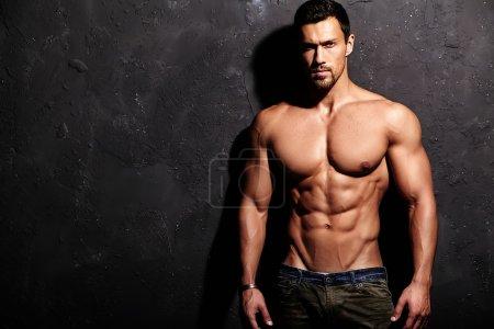 Photo pour Portrait de fort sain bel homme Athletic Fitness Model posant près de mur gris foncé - image libre de droit