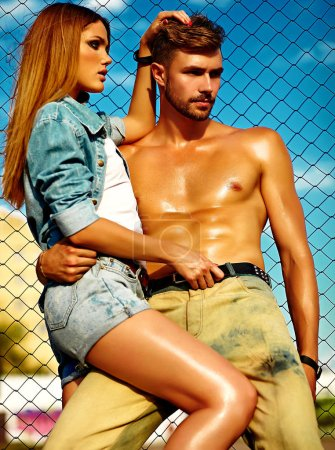 Sexy stylish blond young woman model with bright makeup with perfect sunbathed skin and handsome muscled man in jeans outdoors