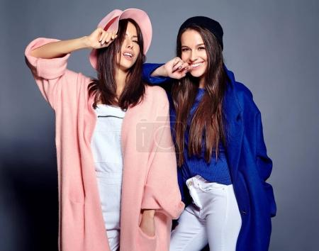 fashion portrait of two smiling brunette women models in summer casual hipster overcoat posing on gray background