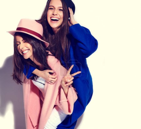 fashion portrait of two smiling brunette women models in summer casual hipster overcoat isolated on white. Girls holding each other on back