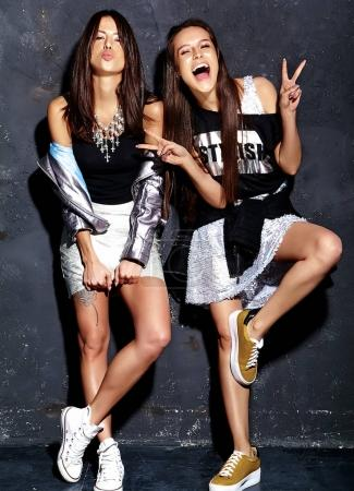 fashion portrait of two smiling brunette models in summer black casual hipster clothes