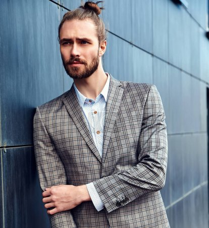 portrait of sexy handsome fashion male model man dressed in elegant checkered suit posing outdoors on the street background