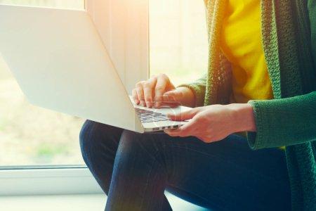 Photo pour Femme tapant sur ordinateur portable tout en étant assis sur le rebord de la fenêtre à la maison - image libre de droit