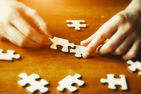 hands solving puzzle jigsaw