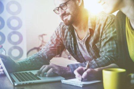 Photo pour Souriant homme et femme travaillant ensemble avec ordinateur portable - image libre de droit