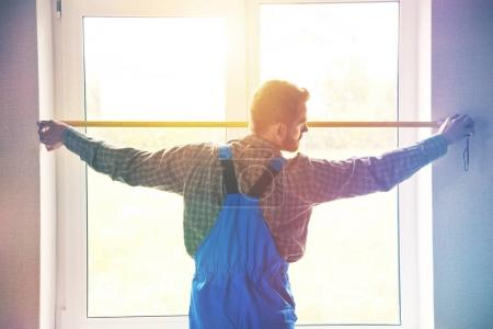 Photo for Service man installing window with measure tape - Royalty Free Image
