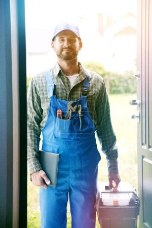 Photo for Portrait of handsome service man with equipment standing on doorstep of the house - Royalty Free Image