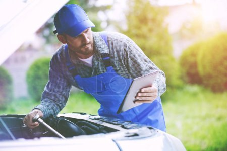 mechanic working with digital tablet