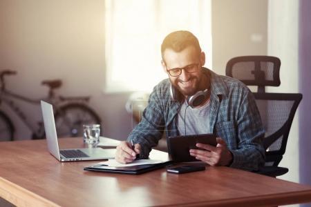 smiling man with digital tablet