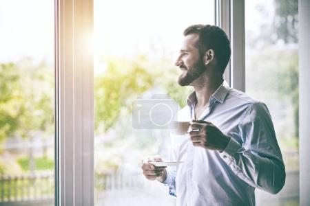businessman holding morning cup of coffee