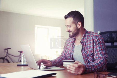 Man holding credit card and using laptop