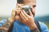 man holding retro camera and taking photo