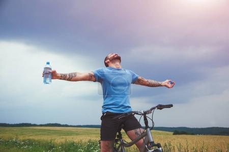 Photo for Happy man with bike spreading hands and drinking water resting. Freedom or happiness concept - Royalty Free Image
