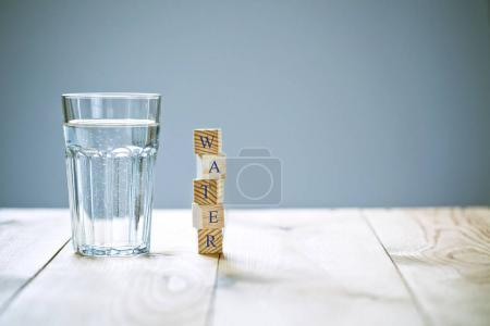 Glass of pure water with word written in wooden blocks