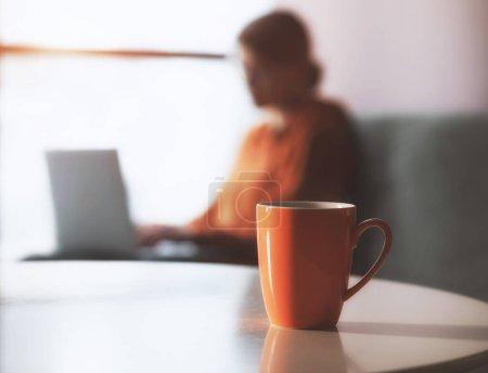 Photo pour Tasse à café ou à thé avec une femme travaillant avec un ordinateur portable à la maison. Lieu de travail confortable sur le canapé. Espace pour tex - image libre de droit