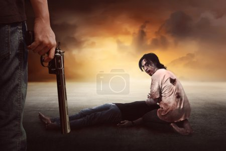 Mann mit Waffe sieht Zombie an