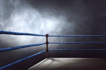 Photo pour Vue d'un anneau de boxe régulier entouré de cordes bleues éclairées par un projecteur - image libre de droit