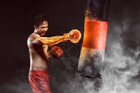 Asian athlete boxer punching a punching bag
