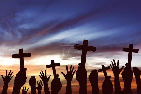 Many hands holding christian cross