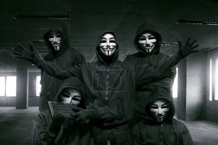 Portrait of hooded hackers in masks holding keyboa...