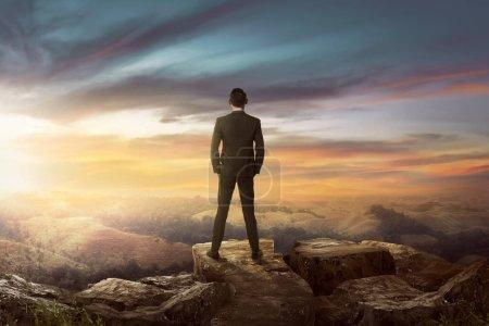 Photo pour Homme d'affaires asiatique debout sur les rochers et la recherche au coucher du soleil - image libre de droit