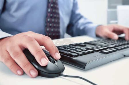 Businessman using computer with hands typing on a keyboard
