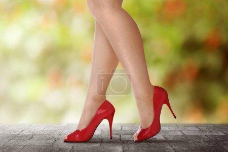 Photo pour Jambes de femme en talons hauts rouges marchant sur la rue urbaine - image libre de droit