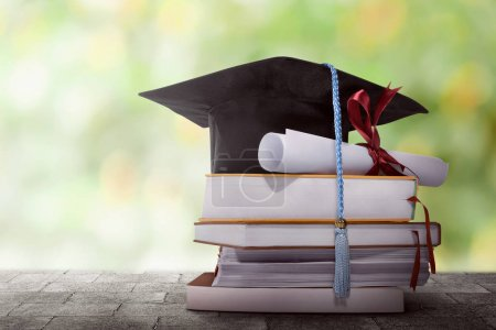 Photo for Graduation hat with degree paper on a stack of books against blurred background - Royalty Free Image