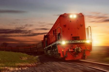 Photo pour Train de marchandises avec wagons transportant du charbon au coucher du soleil - image libre de droit