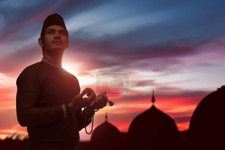 Photo for Religious asian muslim man with prayer beads praying to god over sunset background - Royalty Free Image