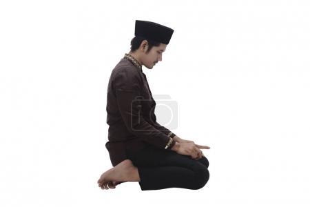 muslim man kneeling while praying