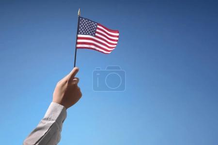 Photo pour Les gens la main tenant le drapeau des Etats-Unis célébrant le 4 juillet contre le ciel bleu - image libre de droit