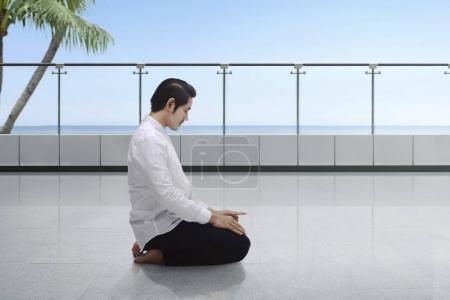 Young asian muslim man kneeling and praying