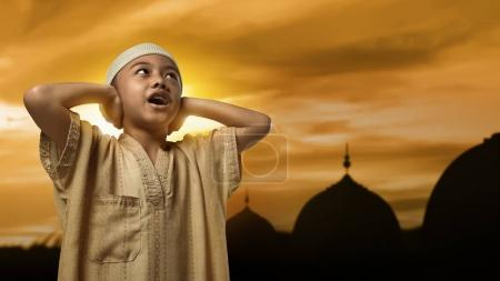 Little asian muslim boy with cap praying