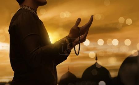Photo pour Homme musulman lever la main et en priant avec perles de prière pendant le coucher de soleil fond - image libre de droit