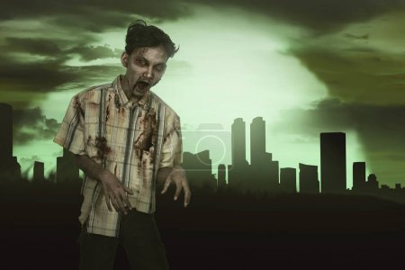 Horrible asian zombie man with blood standing