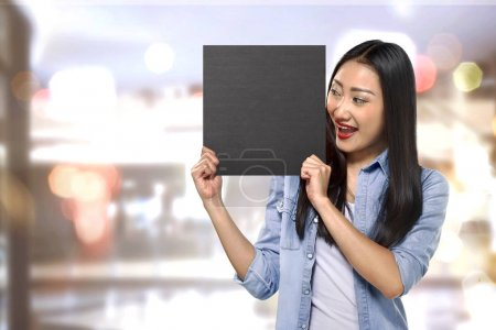 Young asian woman holding sign board with empty space
