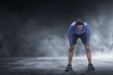 Young asian runner man taking rest