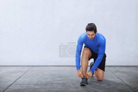 Young asian man tie sport shoe laces