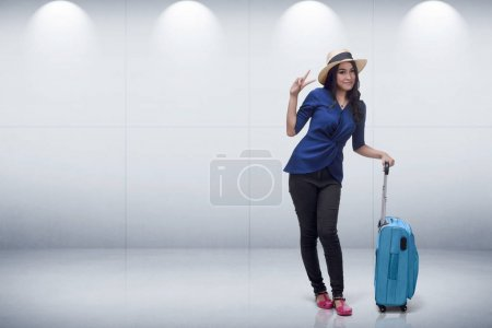 asian woman in hat with a suitcase standing
