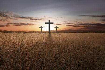 Bright christian cross at sunset