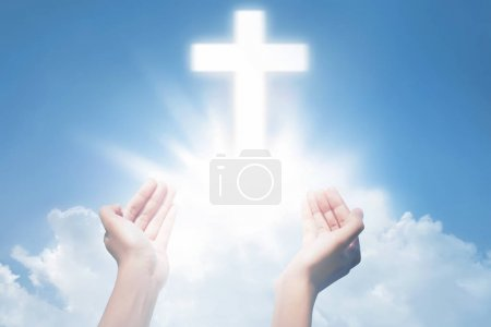 Human hands praying with cross