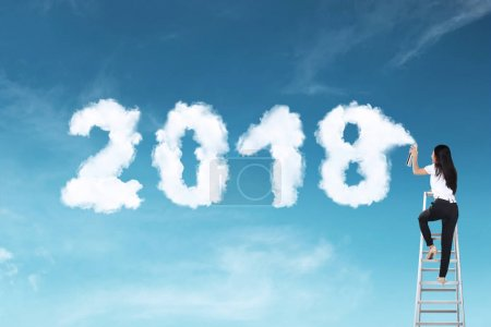 Business woman using stair spraying white cloud with 2018 shape