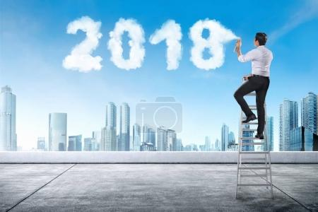 Businessman using stair spraying white cloud with 2018 shape